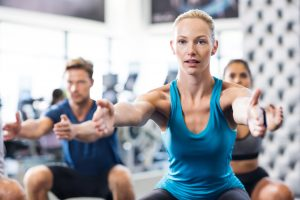 Young woman exercising in gym with people in background. Fit wom
