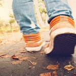 Woman Feet sneakers walking on fall leaves Outdoor with Autumn season nature on background Lifestyle Fashion trendy style