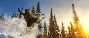 Jumping snowboarder on snowboard in mountains in ski resort on b